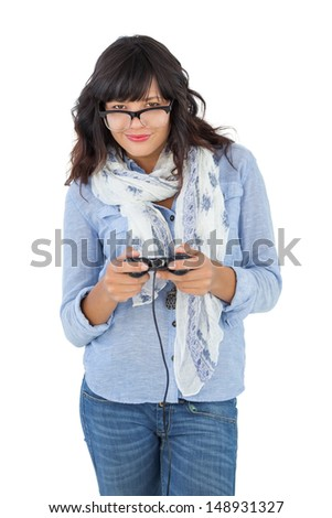 Young woman wearing scarf and glasses playing video games on white background - stock photo