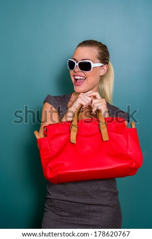 young woman wearing sunglasses looking holding red shopping bag - stock photo