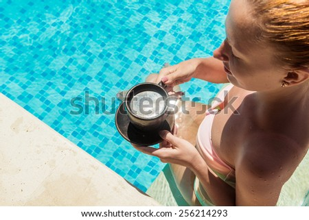 Young woman wearing swimsuit enjoying coffee near swimming pool at exotic location - stock photo