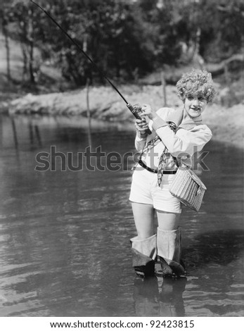 Young woman wearing waders holding a fishing rod - stock photo