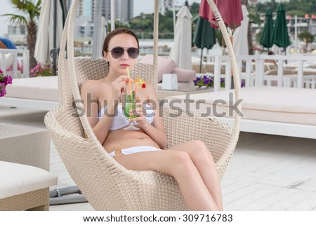 Young Woman Wearing White Bikini and Dark Sunglasses Relaxing in Wicker Deck Chair with Tropical Drink on Patio of Oceanfront Luxury Vacation Resort - stock photo