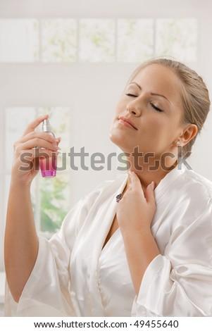 Young woman wearing white silk bathrobe applying perfume, eyes closed. - stock photo