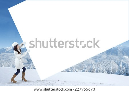 Young woman wearing winter clothes and pulling empty banner for copyspace, shot outdoors - stock photo
