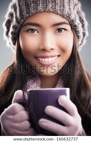 Young woman wearing winter clothes holding a purple mug. - stock photo