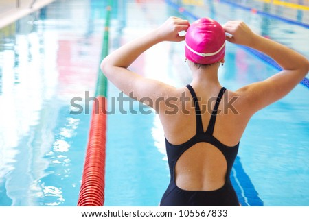 young woman wears glasses in front of the swimming pool. Back. - stock photo