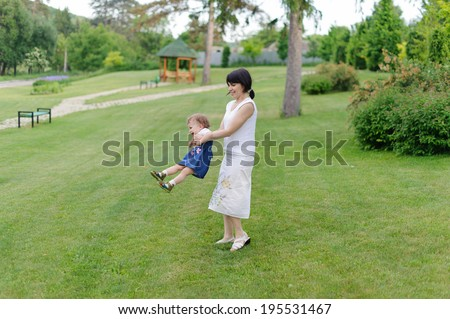young woman whirling her daughter - stock photo