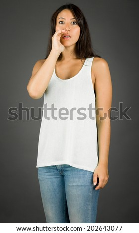 Young woman whispering message with cupping hand over mouth - stock photo
