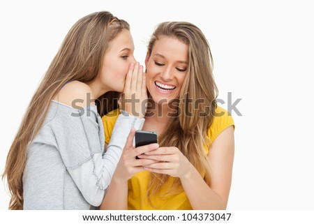 Young woman whispering to her friend who's texting on her phone against white background - stock photo