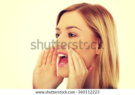Young woman whispers gossip. - stock photo