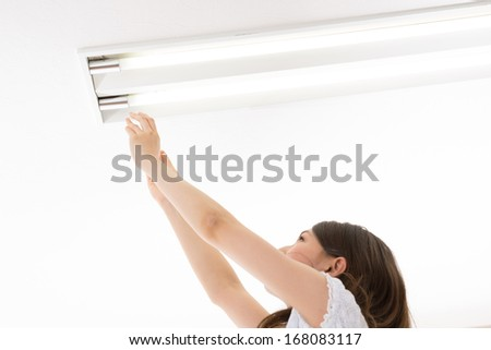 young woman who exchanges a fluorescent lamp - stock photo