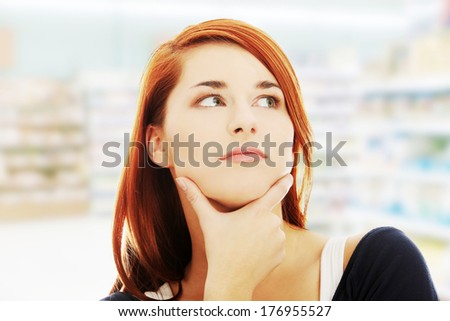 Young woman who is looking to side, wondering and thinking in shop.  - stock photo