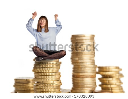 young woman winner sitting on a coins tower - stock photo