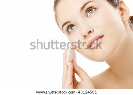 Young woman wipes a face skin, isolated - stock photo
