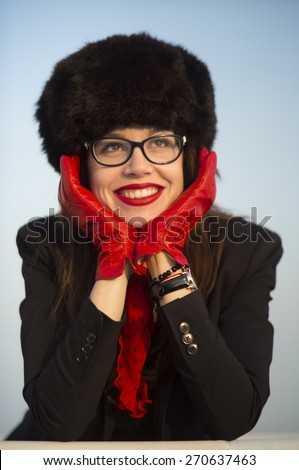 Young woman with a beautiful smile wearing red lipstick and big fur hat on a sunny winter day. - stock photo