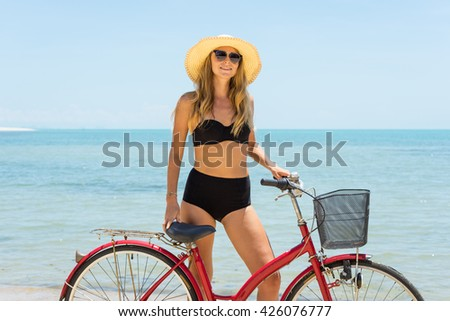 Young woman with a bicycle on a tropical beach - stock photo