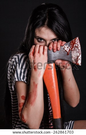 Young woman with a big bloody axe over black background - stock photo