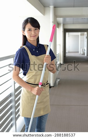 young woman with a broom sweeping the entrance - stock photo