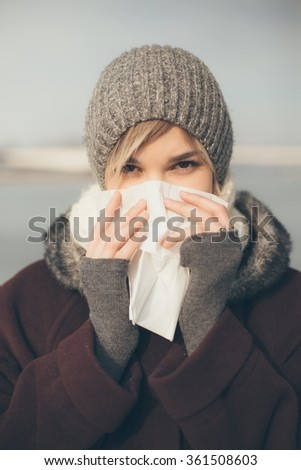 Young woman with a cold holding a tissue - stock photo