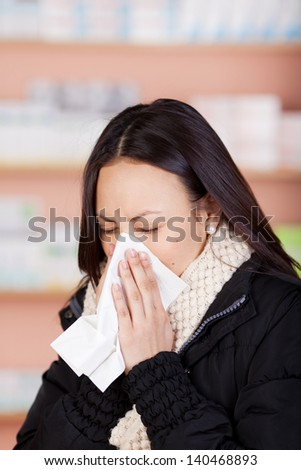 young woman with a cold using paper tissue in pharmacy - stock photo