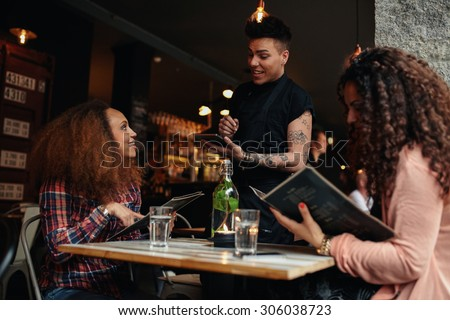 Young woman with a friend ordering to waiter holding digital tablet. Two women sitting at cafe holding menu card giving an order to male waiter. - stock photo