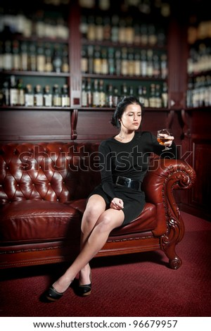 Young woman with a glass of brandy - stock photo