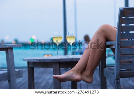 Young woman with a glass of white wine at evening - stock photo