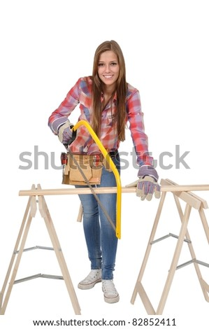 Young woman with a hacksaw sawing a board - stock photo