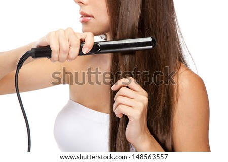 Young woman with a hair straightener, white background - stock photo