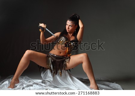 young woman with a knife on a black background. vivid emotions, long beautiful Hair - stock photo
