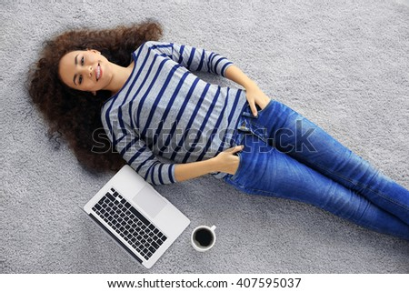 Young woman with a laptop lying on the floor - stock photo