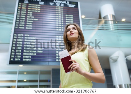 Young woman with a passport at the board - stock photo
