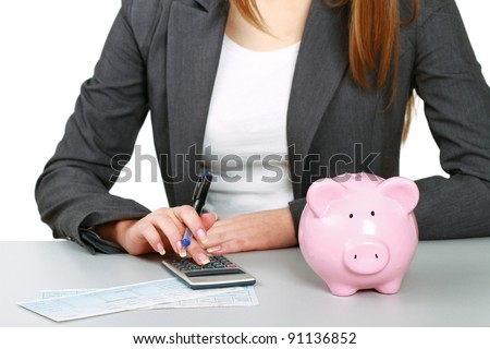 Young woman with a piggy bank and using a calculator - stock photo