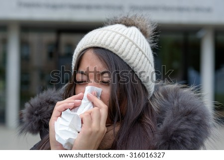 Young woman with a seasonal winter cold or flu wearing a furry jacket and knitted cap blowing her nose on a white handkerchief outdoors on an urban street - stock photo