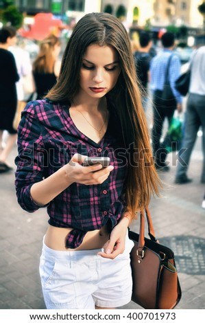 Young woman with a smartphone standing at the street. - stock photo