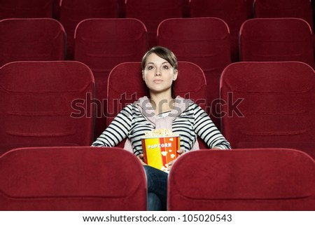 Young woman with a snack food waiting for a friend at the cinema - stock photo