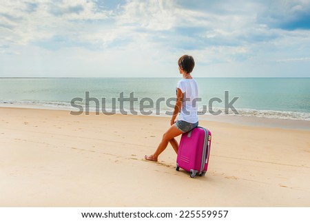 Young woman with a suitcase on the beach - stock photo