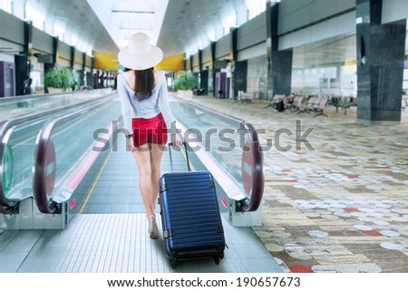 Young woman with a suitcase walking to escalator at airport - stock photo