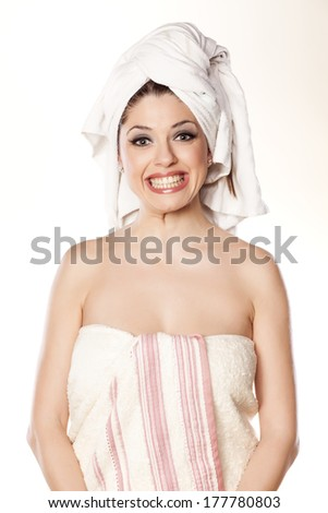 young woman with a towel on her head with a false smile on her face - stock photo