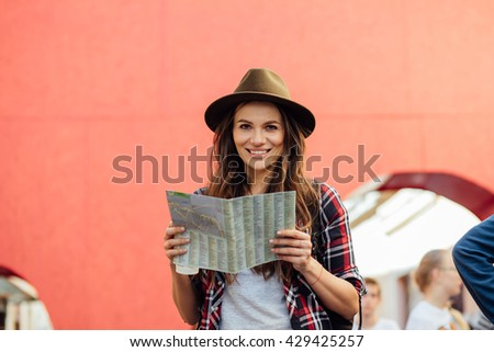 young woman with a vintage hat, traveling and exploring old city, with people on the streets, having a backpack and a coffee in hands - stock photo