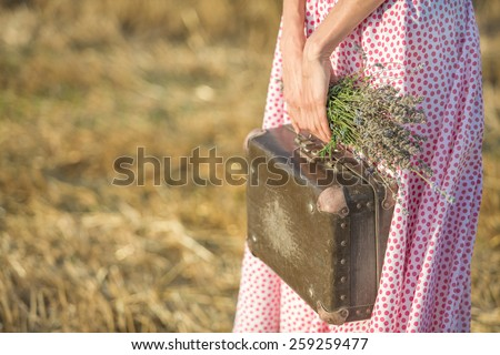 Young woman with a vintage suitcase. shallow depth of view, focus on flowers - stock photo
