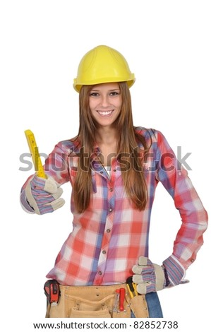 Young woman with a yellow helmet holds up a ruler - stock photo