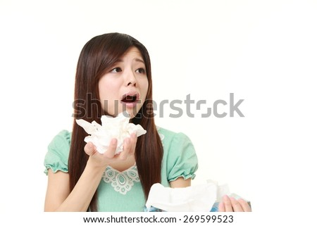 young woman with an allergy sneezing into tissue - stock photo