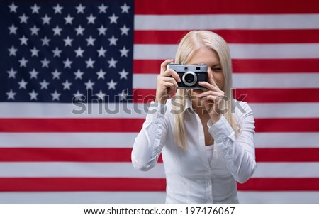 Young woman with an American flag and a camera - stock photo