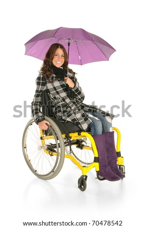 Young woman with an umbrella in a wheelchair - stock photo