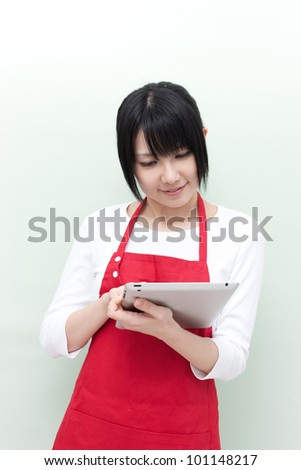 young woman with apron using a tablet computer - stock photo