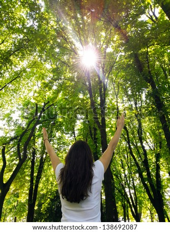 Young woman with arms raised enjoying the fresh air in green forest - stock photo