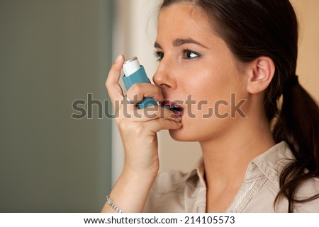 Young woman with asthma inhaler. - stock photo