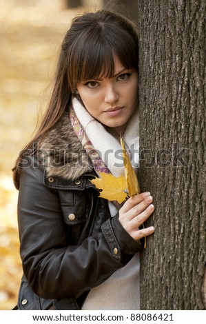 Young woman with autumn leaf in hand in autumn forest - stock photo