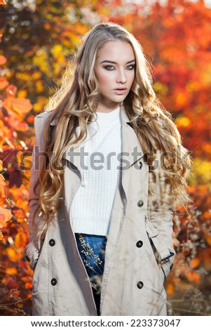 Young woman with autumn leaves  fall yellow garden background - stock photo