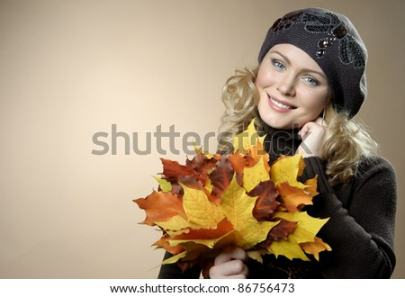 Young woman with autumn leaves in hand - stock photo